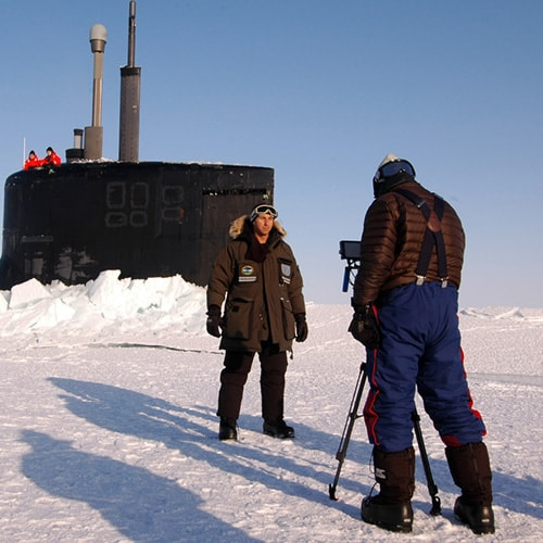 Two people conducting a video interview in a winter landscape